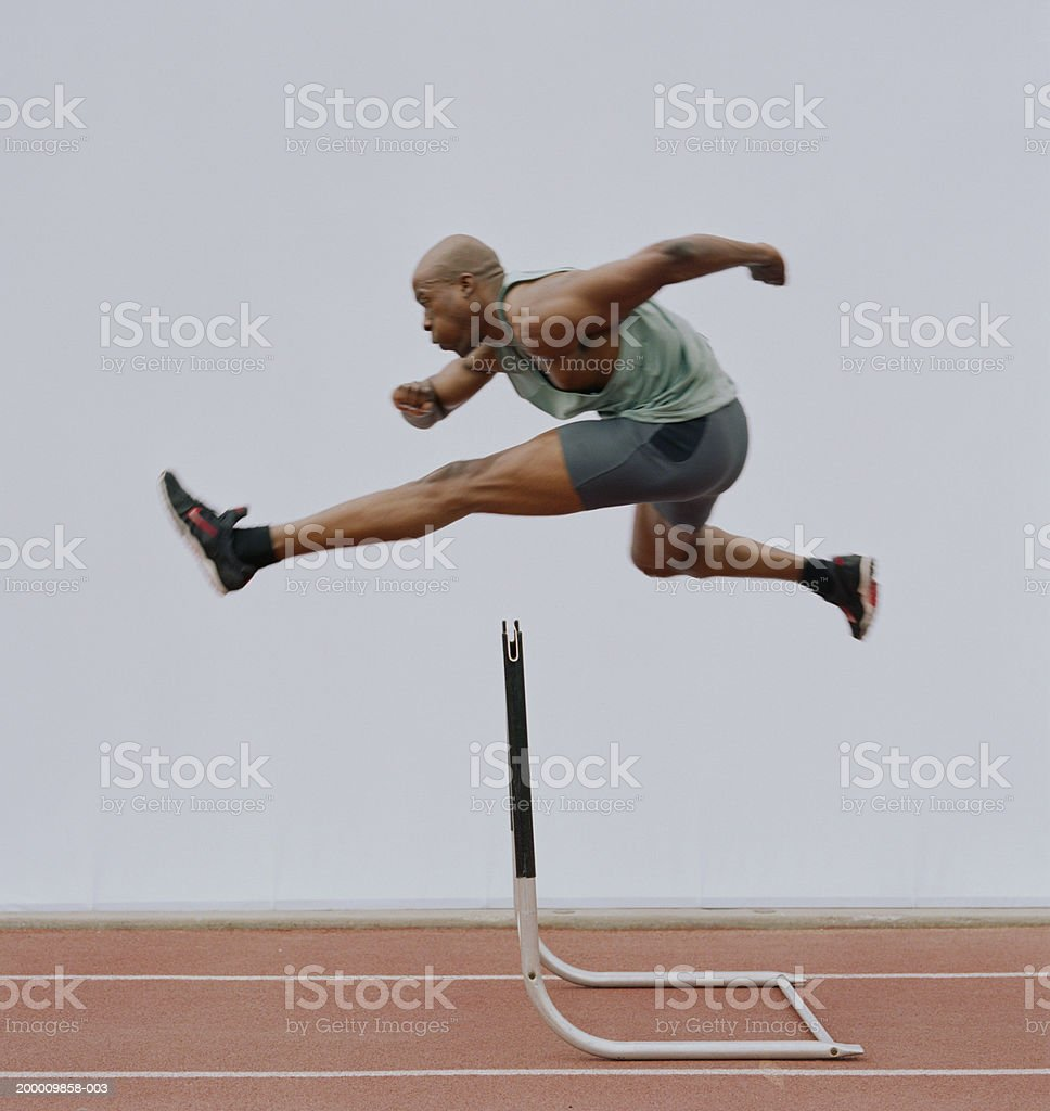 Man jumping hurdle, side view stock photo
