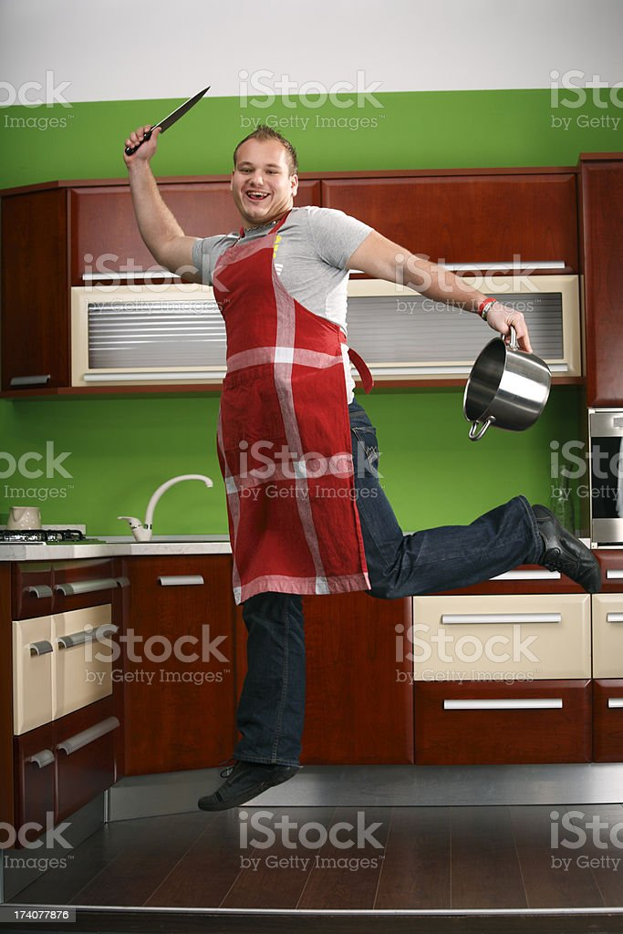 Man jumping in kitchen, cherry wood panel royalty-free stock photo