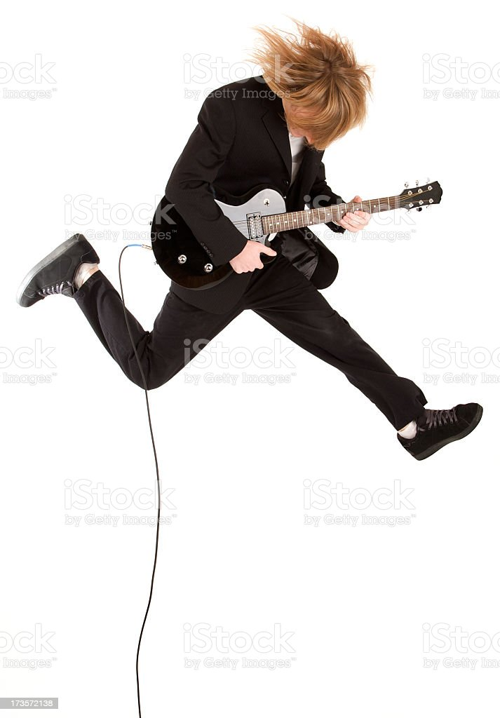 A man jumping in the air playing his electric guitar royalty-free stock photo