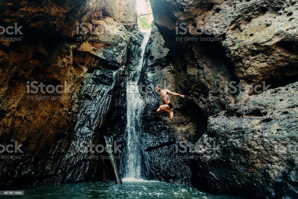 Man jumping into tropical waterfall stock photo