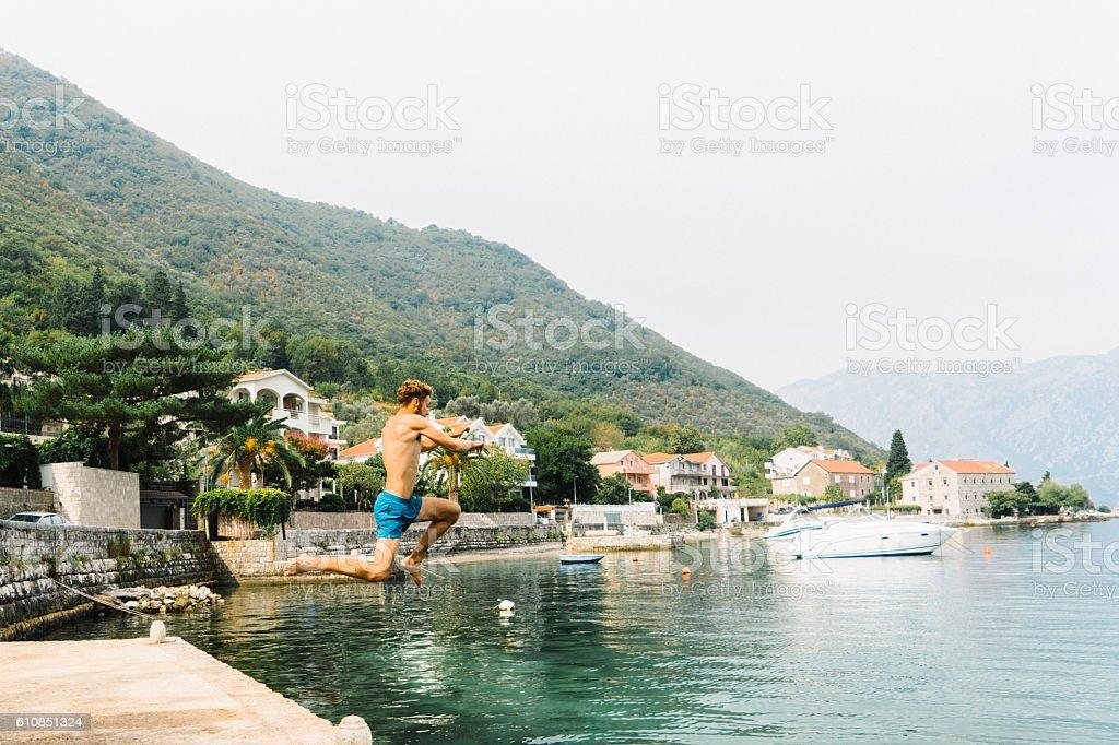 Man jumping into water,  Kotor bay stock photo