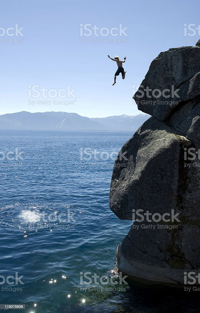 Man jumping off a cliff into the sea stock photo