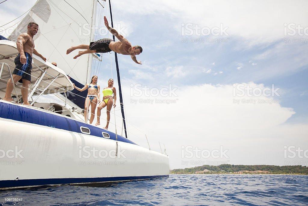 Man jumping off sailboat into Caribbean Sea stock photo