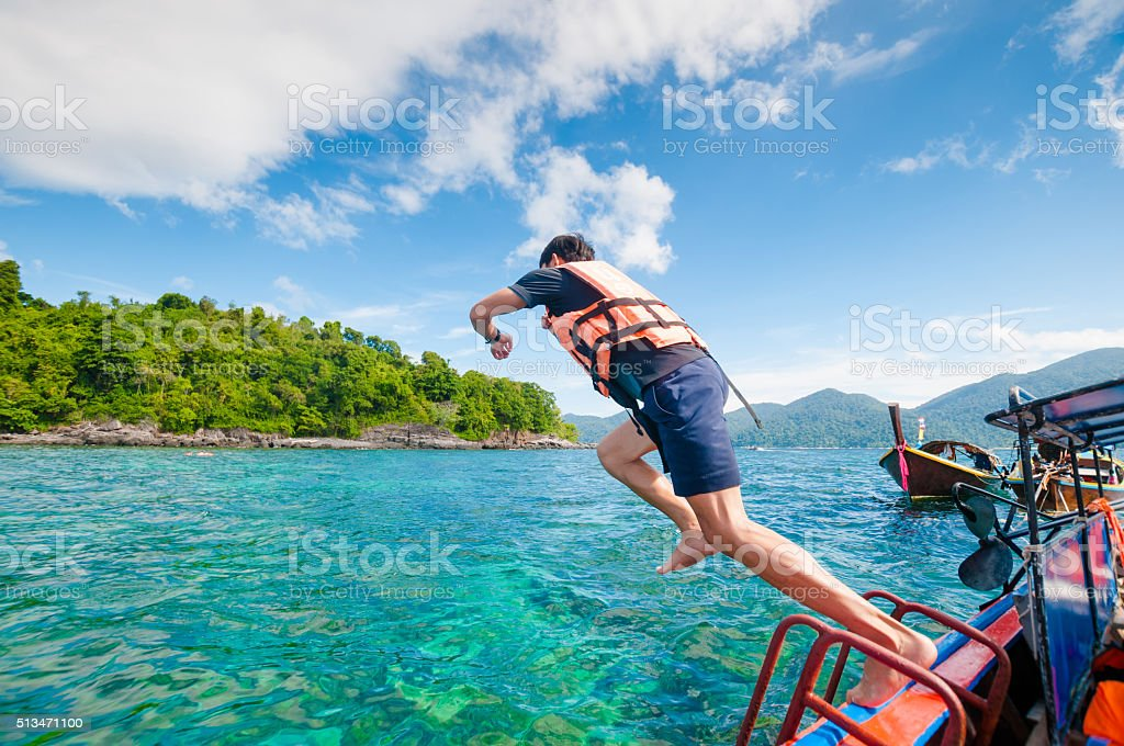 Man jumping off the boat into the ocean stock photo