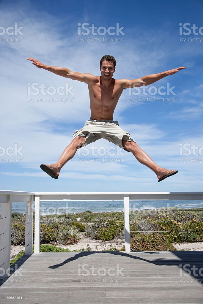 A man jumping off the rail of a terrace stock photo