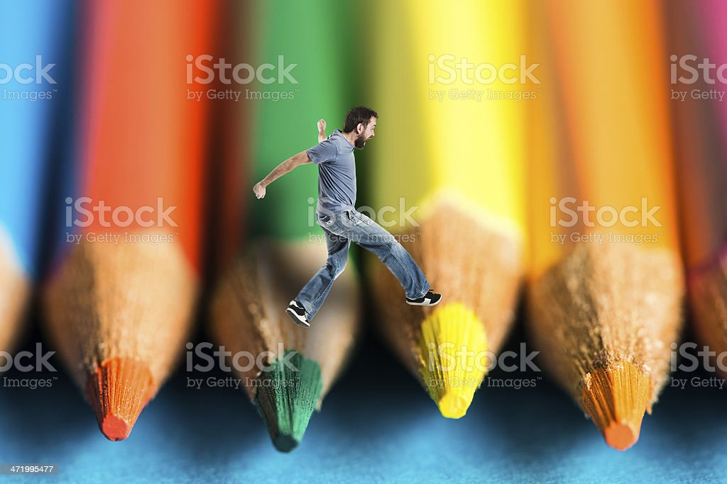 Man jumping on crayons stock photo