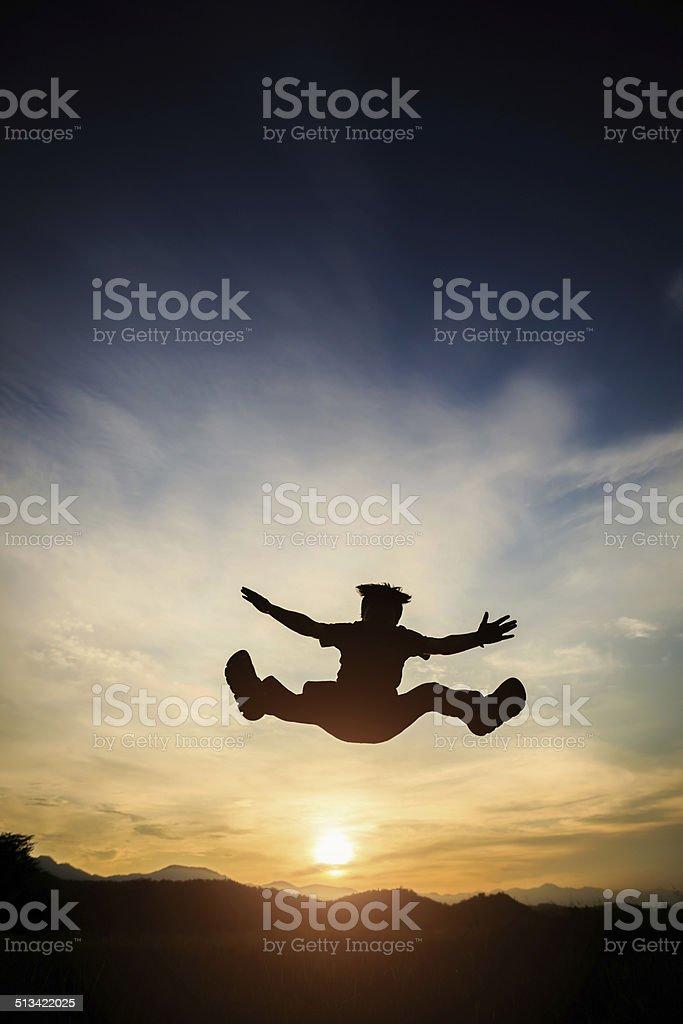 Mann, springen über Sonnenuntergang Lizenzfreies stock-foto