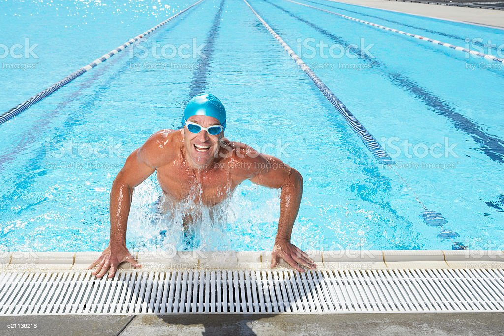 Man jumping out of swimming pool stock photo