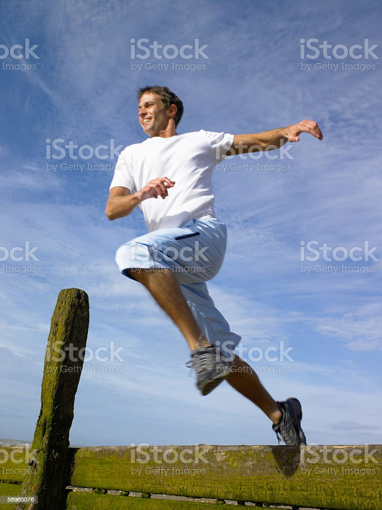 Man jumping over a fence stock photo