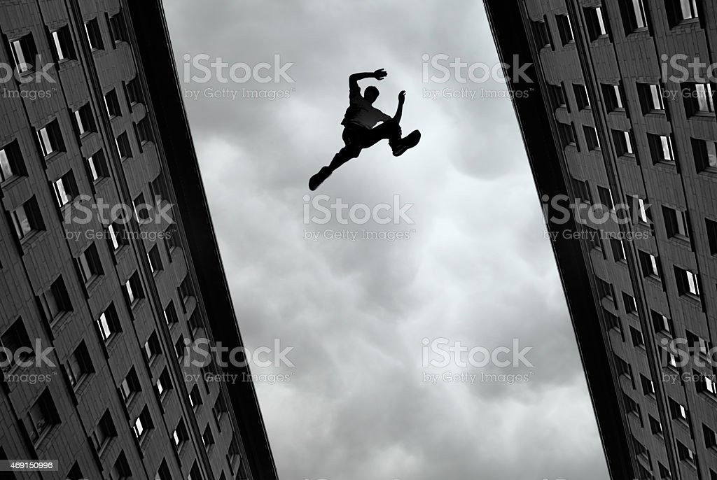 Man jumping over building stock photo