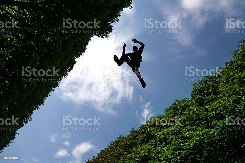 Man jumping over bushes stock photo