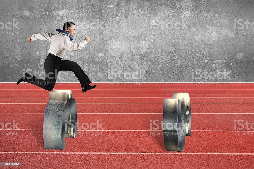 Man jumping over currency symbol obstacles on track stock photo