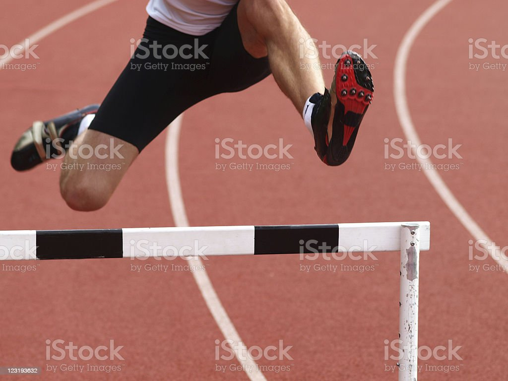 Man jumping over hurdle stock photo