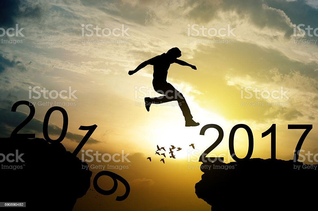 Man jumping over precipice on sunset background , 2017 new year stock photo
