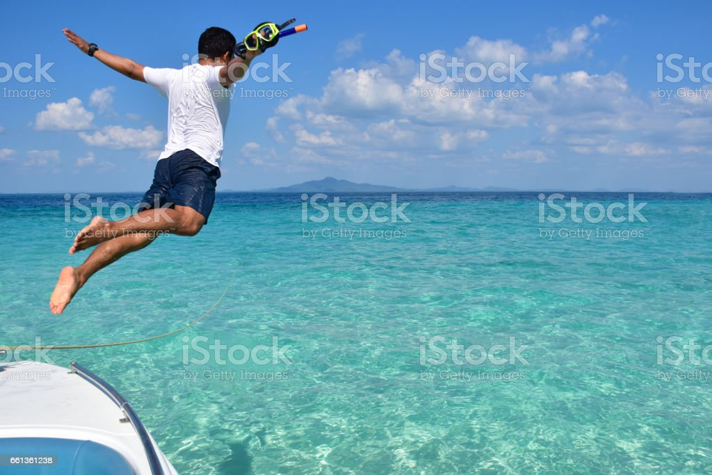 man jumps into the sea on his holiday stock photo