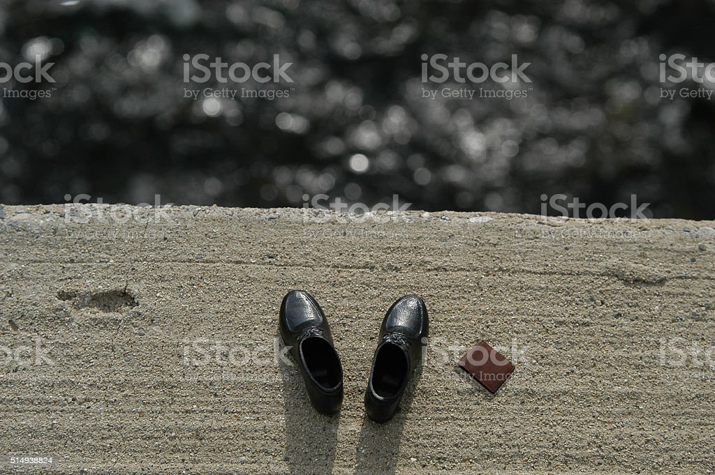 Man jumps off a bridge leaving this black shoes behind stock photo