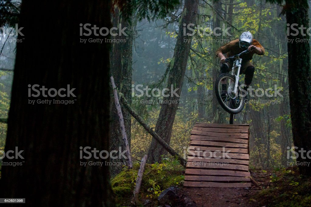 A man jumps off a wooden bridge on his downhill mountain bike on a foggy day in British Columbia, Canada. stock photo