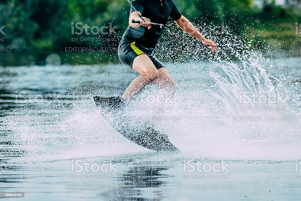 man jumps on wakeboard wave stock photo