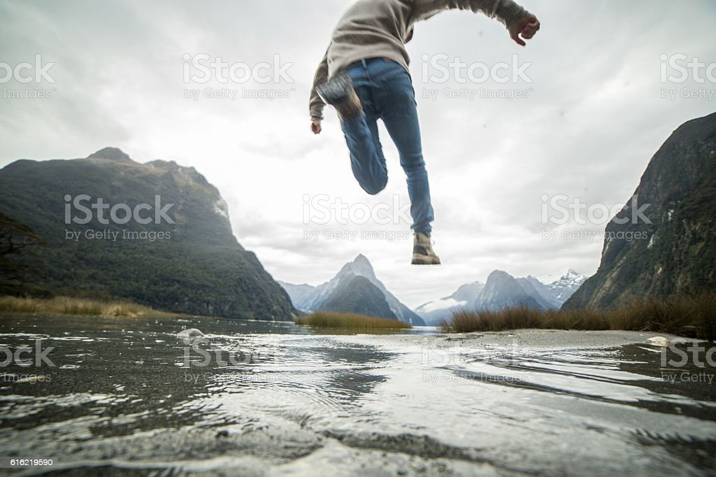 Man jumps over mountain river stock photo