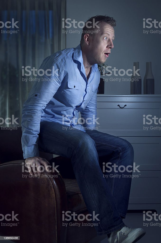 Man jumps up out of his chair stock photo