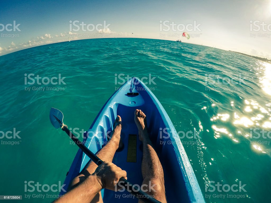 POV Man kayaking in the ocean at midday stock photo