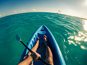 POV Man kayaking in the ocean at midday