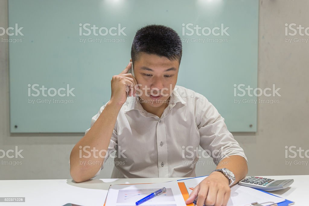Man keeping his eyes on report and answer the phone stock photo