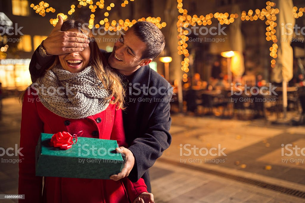 Man keeps girlfriend eyes covered while  she giving a gift stock photo