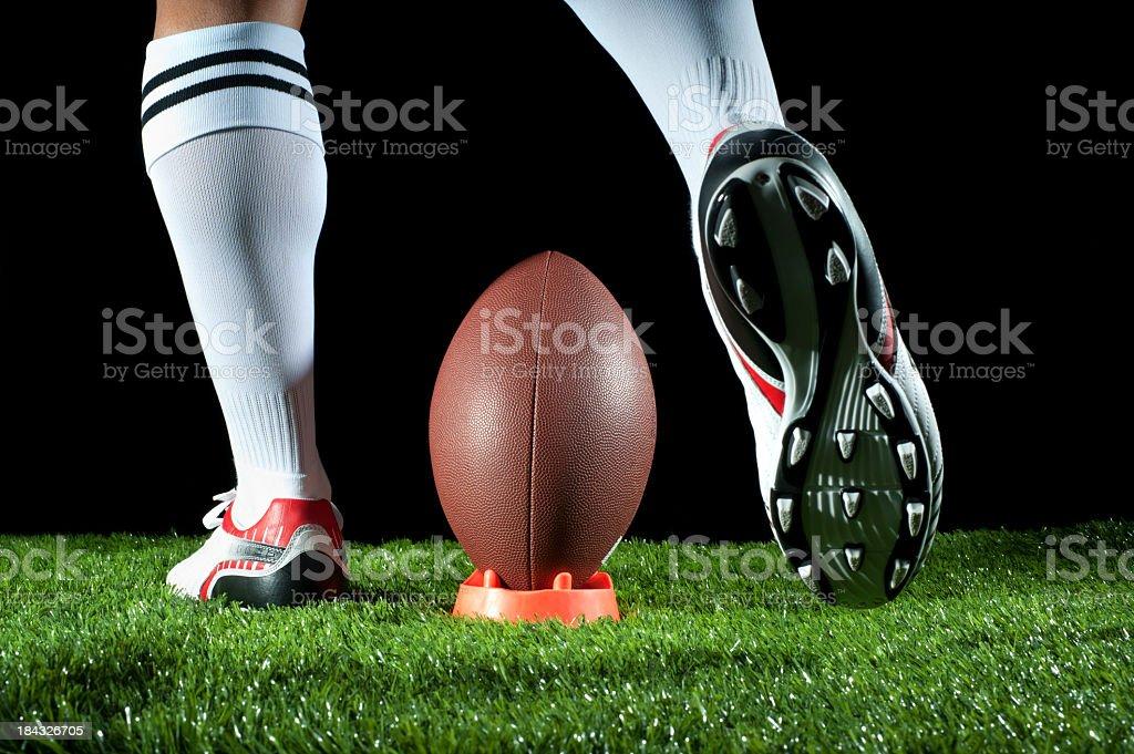 Man kicking an American football stock photo