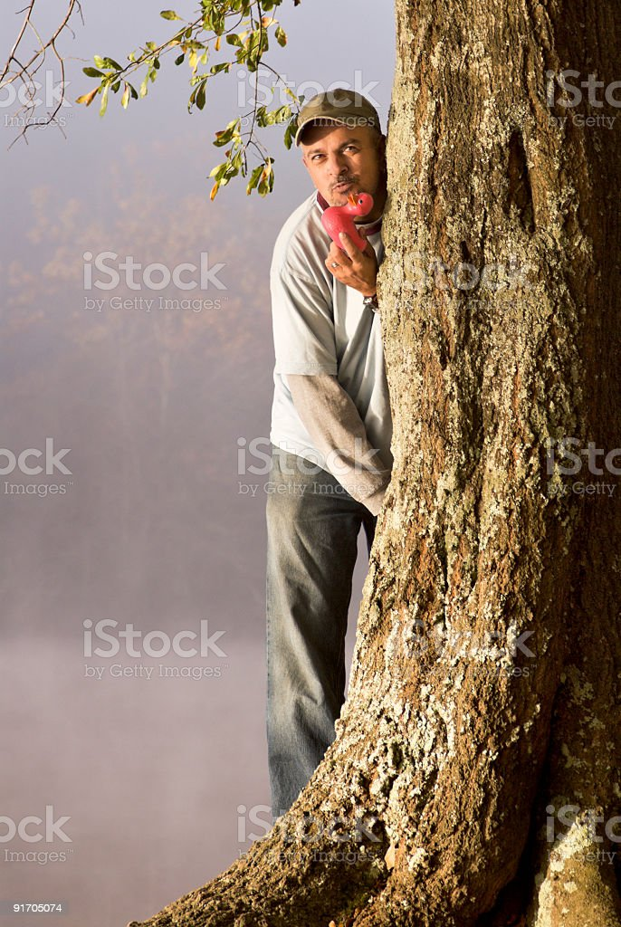 man kissing a rubber duck behind a big oak tree royalty-free stock photo
