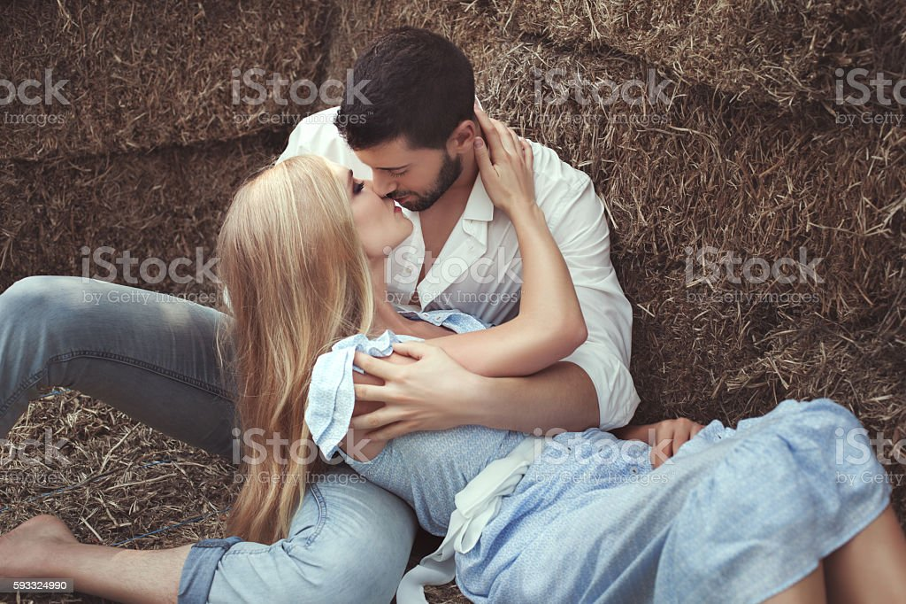 Man kissing a woman in the hayloft. stock photo