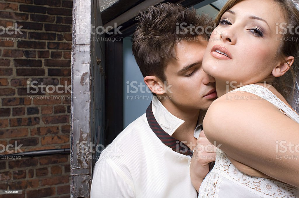 A man kissing a woman on the neck stock photo