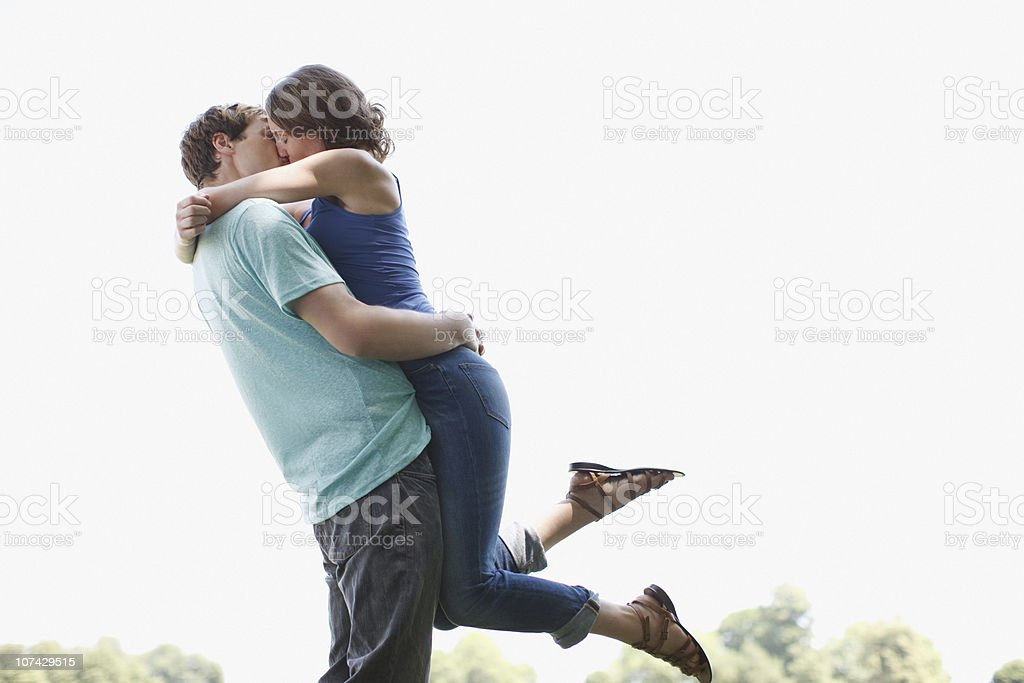 Man kissing and lifting wife outdoors stock photo