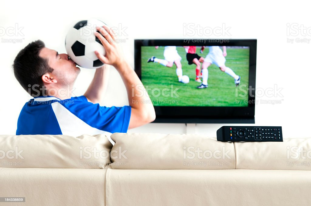 A man kissing his soccer ball while watching soccer on TV royalty-free stock photo