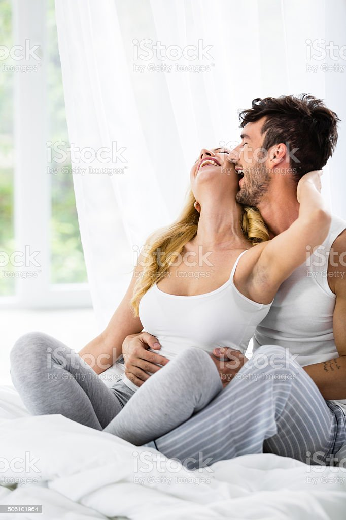 Man kissing woman in bed stock photo
