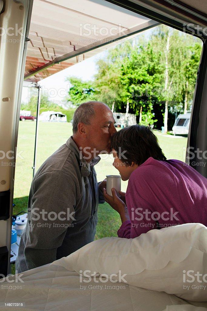 Man kissing woman in camper van stock photo