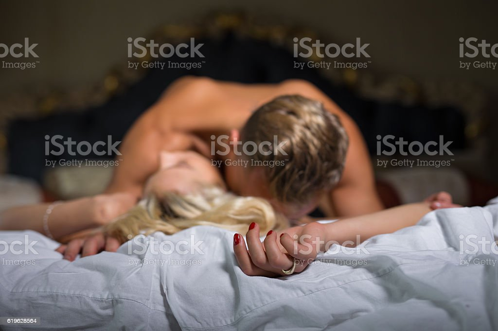 Man kissing womans neck while she is lying down stock photo