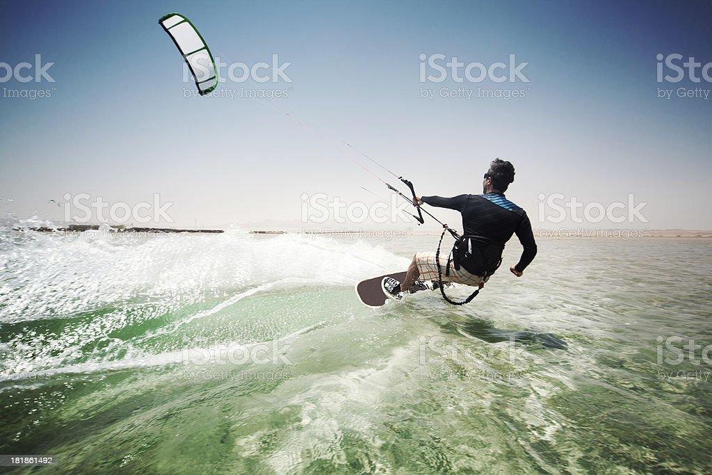 Man kiteboarding on choppy waves stock photo