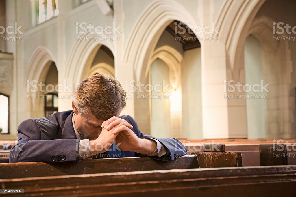 Man Kneeling and Praying in Church stock photo