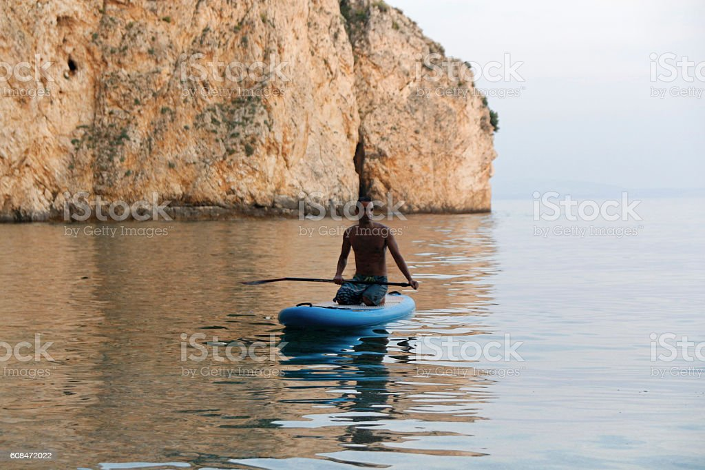 Man kneeling on a stand up paddle board stock photo