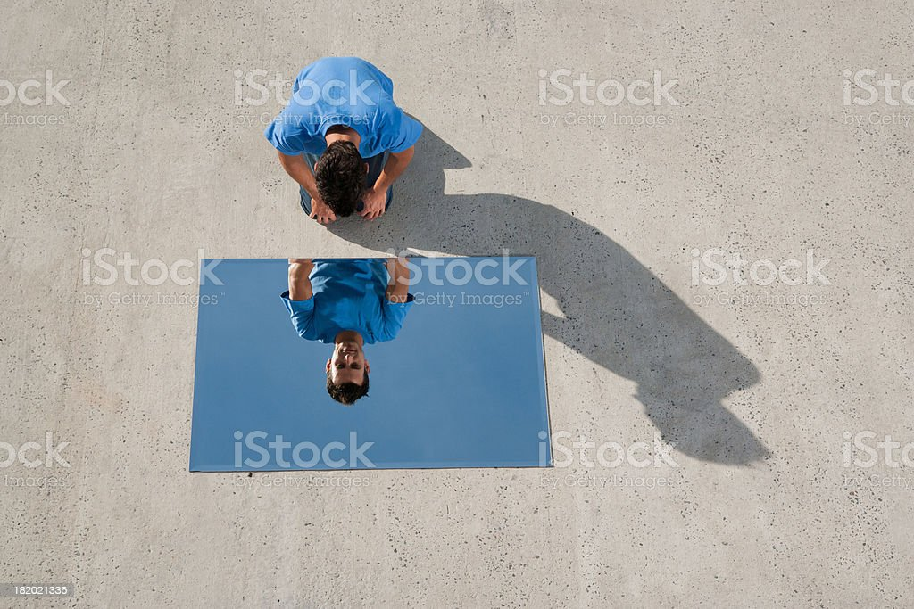 Man kneeling on ground with mirror and reflection stock photo