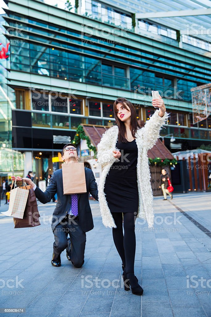 Man kneels on one knee down and holds shopping bags stock photo