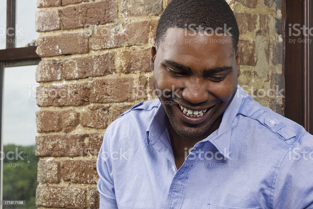 Man Laughing with His Eyes Down stock photo