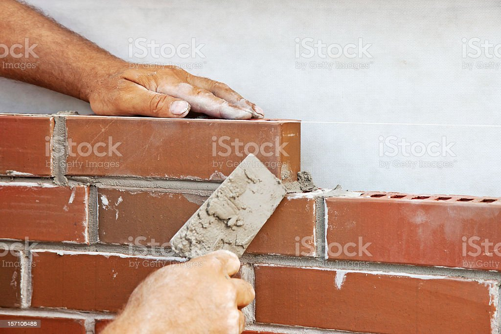 Man laying bricks on a new house stock photo