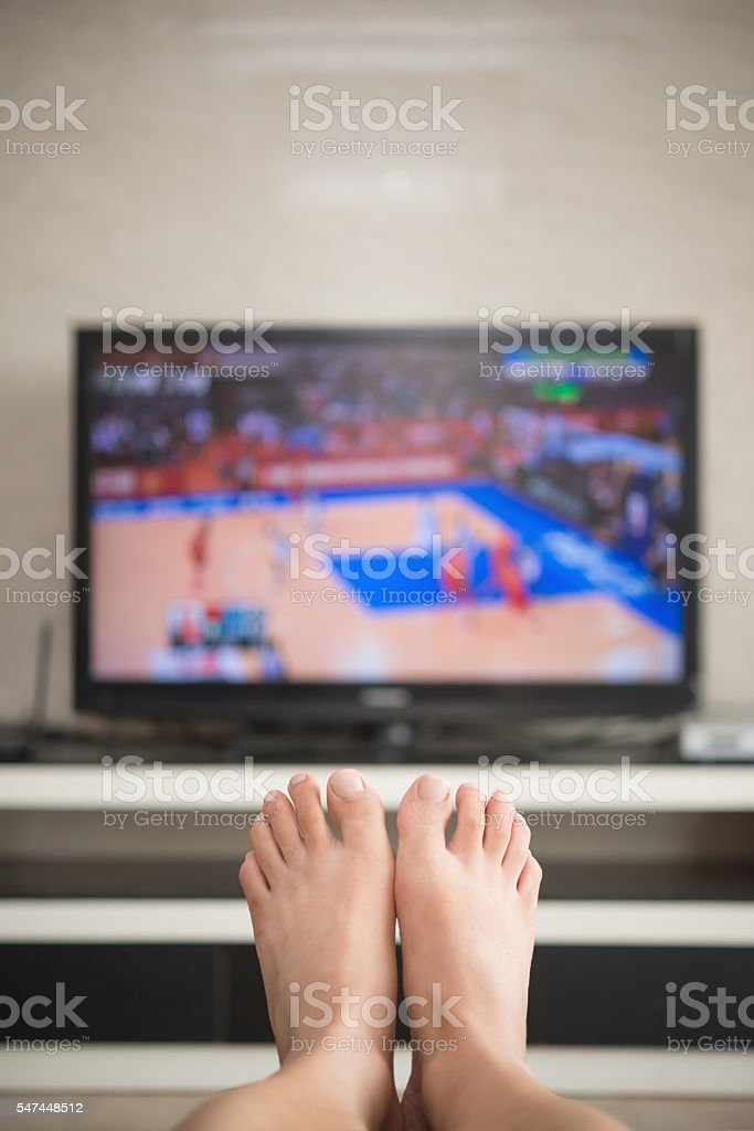 man laying down on a sofa at home watching tv stock photo