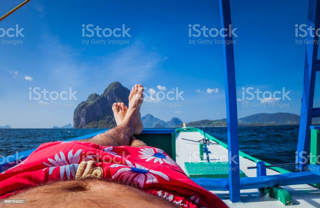Man laying in banca boat, feet facing Inabuyatan Island by El-Nido, Palawan, Philippines stock photo