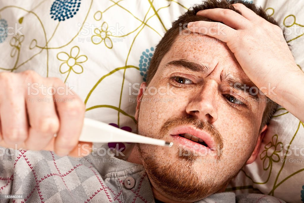 A man laying in bed measuring his fever royalty-free stock photo