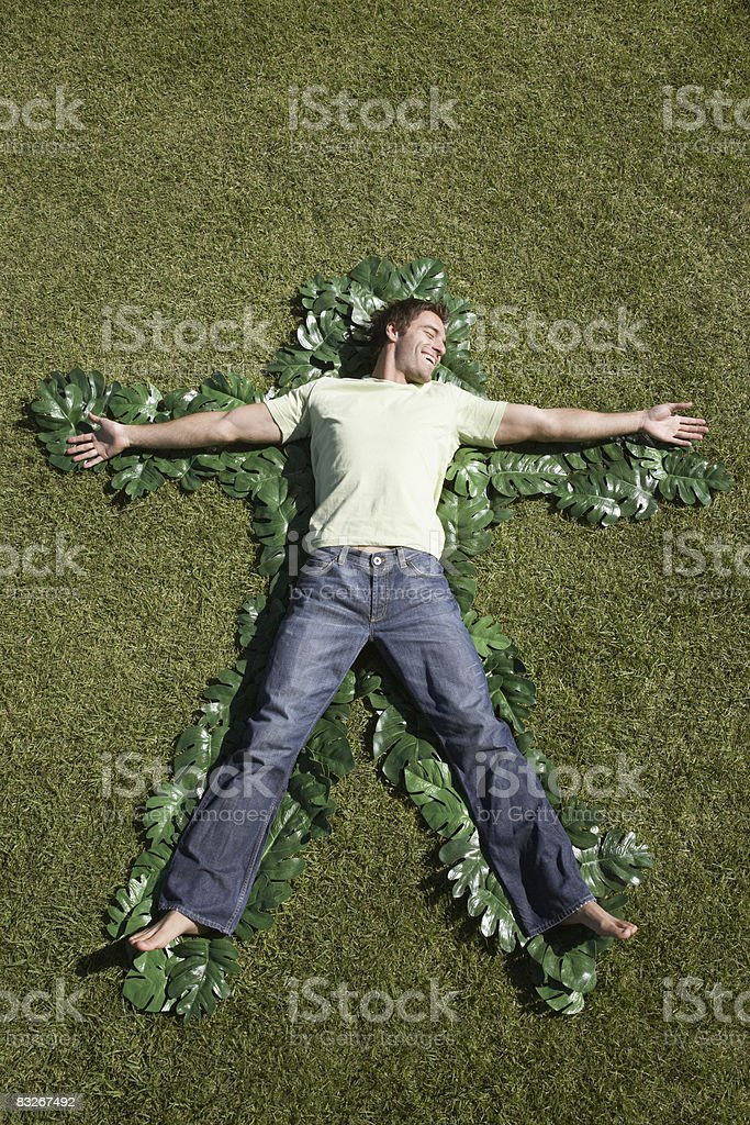Man laying in grass outlined by green leaves royalty-free stock photo