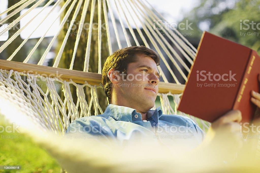Man laying in hammock reading book royalty-free stock photo