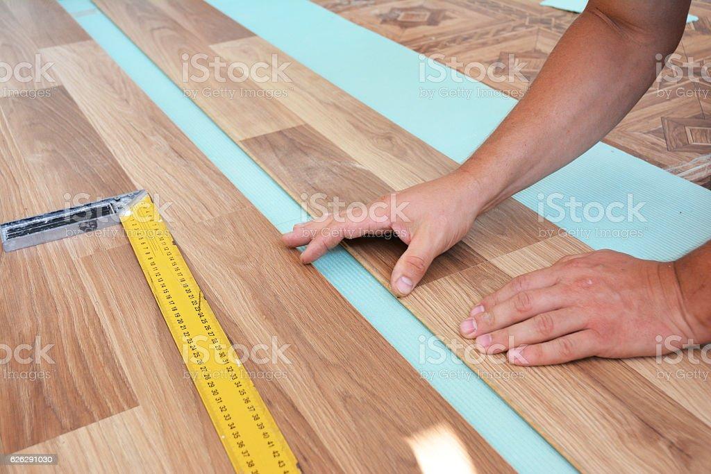 Man laying laminate flooring. Step by Step. stock photo